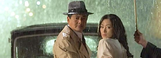 Shanghai's Chow Yun-Fat and Gong Li look over shoulders as umbrella shields them from rain