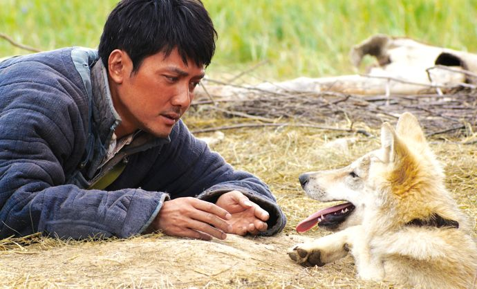 Wolf Totem's Feng Shaofeng lies close to his wolf cub