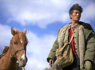 Wolf Totem's Shawn Dou stands beside horse in Mongolian grassland