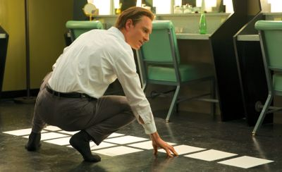 Steve Jobs' Michael Fassbende on his haunches spreads sheets of paper on floor