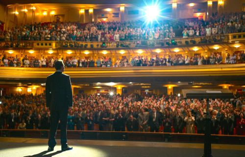 Michael Fassbender's Steve Jobs stands on stage in front of large audience