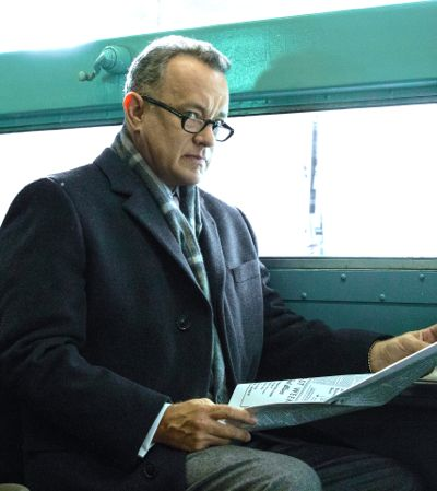 Bridge of Spies' Tom Hanks looks up with concern from newspaper as he rides NYC subway