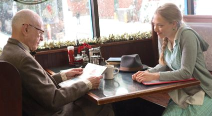 Meet the Coopers' Alan Arkin and Amanda Seyfried sit at diner table next to window