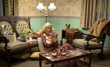 Carol's Cate Blanchett sits on living room floor with a drink in hand