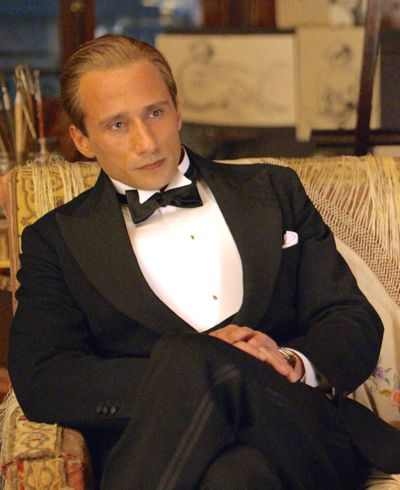 Danish Girl's Matthias Schoenaerts in tux sits languidly on golden couch