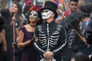 Spectre's Daniel Craig and Stephanie Sigman in costume amid Day of Dead crowd