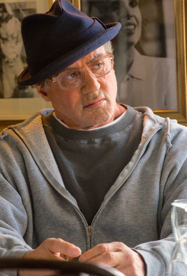 Creed's Sylvester Stallone with glassess studies a young man coming to him for help
