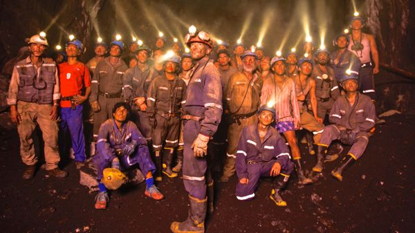 The 33 Chilean miners stand in underground mine all with helmet lights on