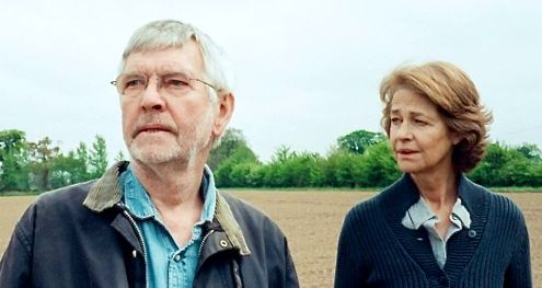 45 Yearas' Tom Courtenay, Charlotte Rampling gaze off camera while standing in English countryside