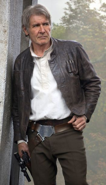 Star Wars' Harrison Ford leans against wall with gun in right hand