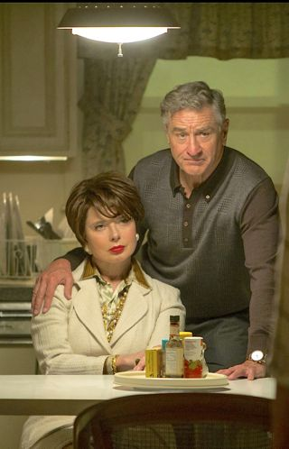 Joy's Robert De Niro stands next to seated Isabella Rossellini with right hand on her shoulder