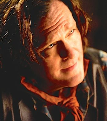 Hateful Eight's Michael Madsen in wester clothes smiles slyly