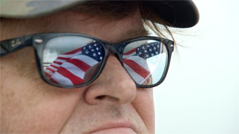 Where ti Invade's Michael Moore has US flag reflect in his eyeglasses