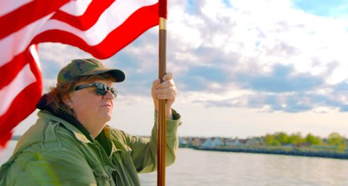 Where to Invade Next's Michael Moore carries American flag on boat