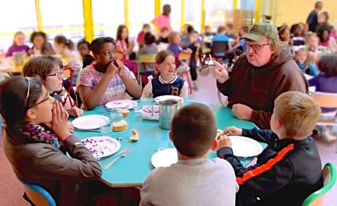 Where to Invade's Michael Moore sits with French school children at lunch