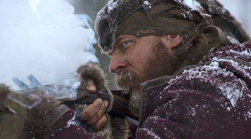 Revenant's Tom Hardy sights prey with his rifle in icy wilderness
