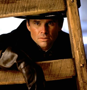 Hateful Eight's Walton Goggins looks out from behind wooden chair