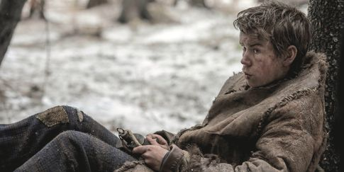 Revenant's Will Poulter leans back against tree while holding a rope