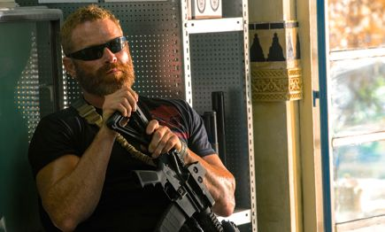 13 Hours' Max Martini leans back against wall near window with his gun