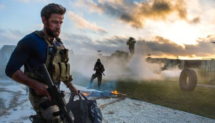 13 Hours' John Krasinski carries his gear and weapon toward his defensive post during seige of Benghazi