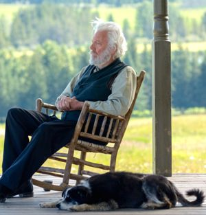 Forsaken's Donald Sutherland sits on porch in rocking chair with dog beside him