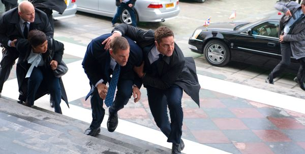 London Has Fallen's Gerard Butler shields Aaron Eckhart as bullets fly near St. Paul's steps