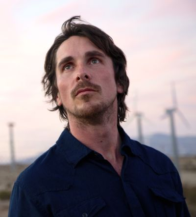 Knight of Cup's Christian Bale stares at distance in field of wind turbines