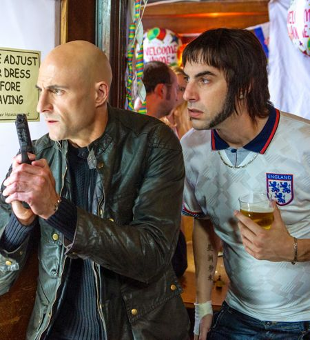 Brothers Grimsby's Mark Strong opens pub door with gun in hand as Sacha Baron Cohen peers over his shoulder