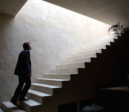 Knight of Cup's Christian Bale mounts interior steps toward bright light