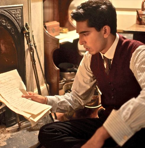 Man Who Knew Infinity's Dev Patel reads papers in front of fire place