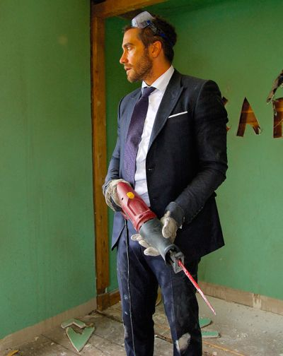 Demolition's Jake Gyllenhaal holds power tool to dismantle interior of a house
