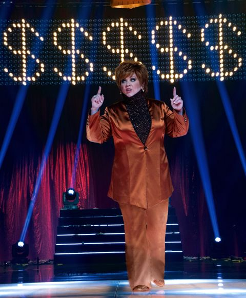 The Boss' Melissa McCarthy performs on stage as self-help guru in front of dollar signs