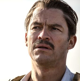 Genius' Dominic West as Ernest Hemingway looks to his left