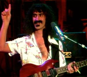 Old photo of Frank Zappa in concert holding guitar and raising his right hand