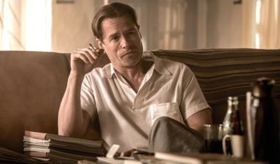 Genius' Guy Pearce as F. Scott Fitzgerald sits on sofa smoking a cigarette