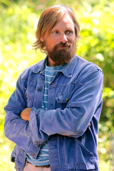 Captain Fantastic's Viggo Mortensen stand in jeans jacket with arms folded in sunny outdoors