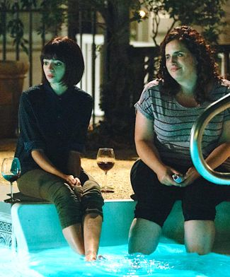 Don't Think Twice's Kate Micucci, Tami Sagher dangle feet in swimming pool as they drink red wine