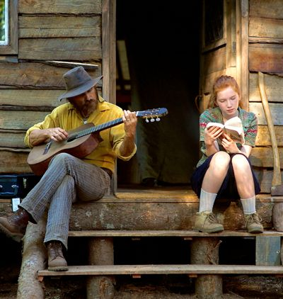 Captain Fantastic's Viggo Mortensen playing guitar and Annalise Basso reading book sit on cabin's wooden steps