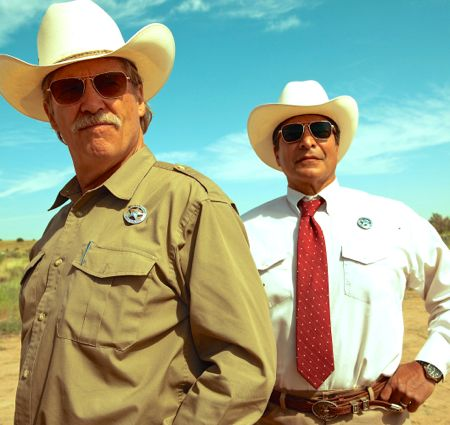 Hell or High Water's Texas Rangers, Jeff Bridges and Gil Birmingham, stand near each other and stare into dusty plains