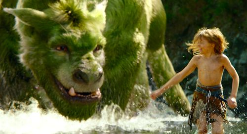 Pete's Dragon's Oakes Fegley splashes in water with large pet dragon