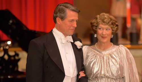 Florence Foster Jenkins' Meryl Streep in gaudy opera costume stands next to Hugh Grant in tux and tails