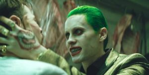 Suicide Squad's Jared Leto grins as he grasps a man'a head