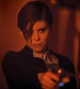 Kate Mara, playing a corporate troubleshooter, points her gun