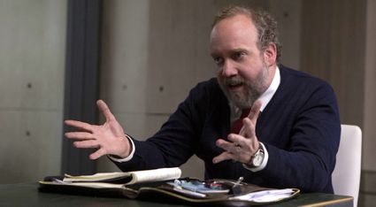 Psychologist Paul Giamatti sits at table conducting interview with non-human being