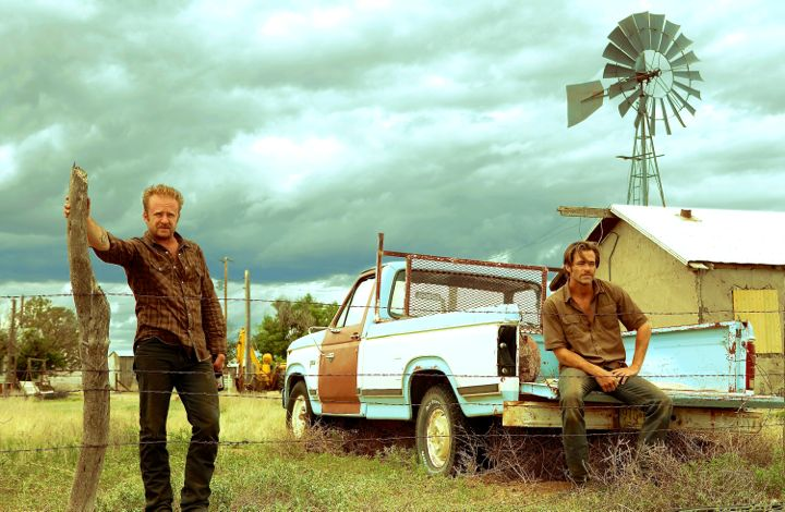 Hell or High Water's Chris Pine, Ben Foster plses in fron of pickup truck on family dirt farm