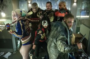 Super villains of DC Entertainment's Suicide Squad pose with weapons