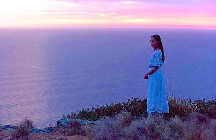 Light Between Ocean's Alicia Vikander stands on island high point staring at sea at sunset