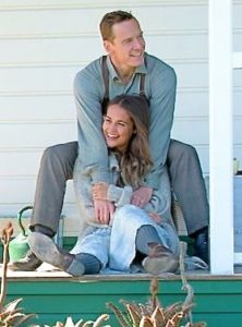 Light Between Ocean's Michael Fassender puts arm around Alicia Vikander as couple sits on porch