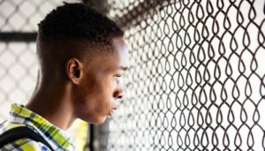 Moonlight's Ashton Sanders gazes through iron mesh fence