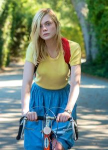 20th Century Women's Elle Fanning bicycles down shady street